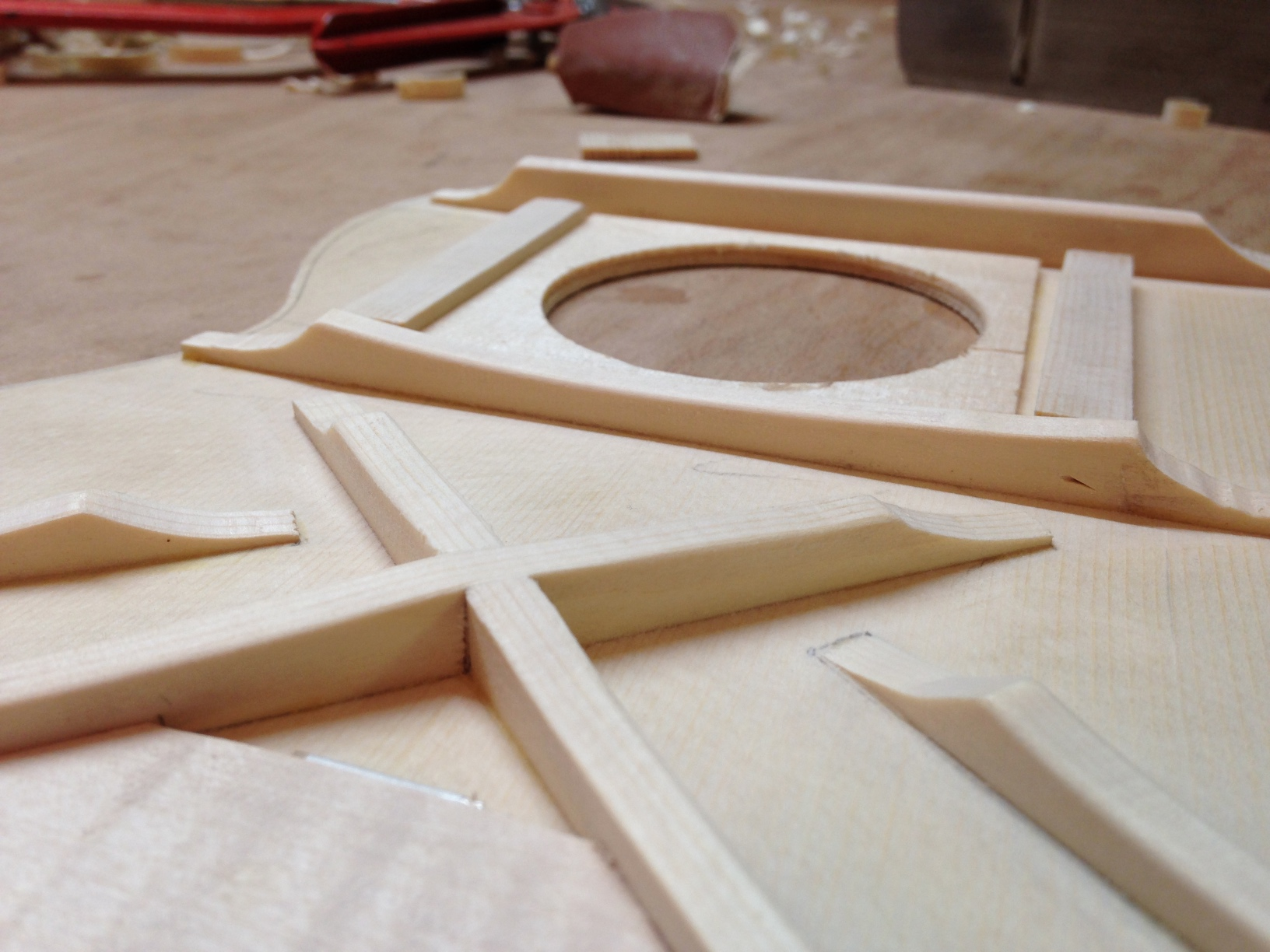 The photo shows the underside of a small guitar-shaped musical instrument soundboard, with traverse and X bracing as well as soundhole support.
