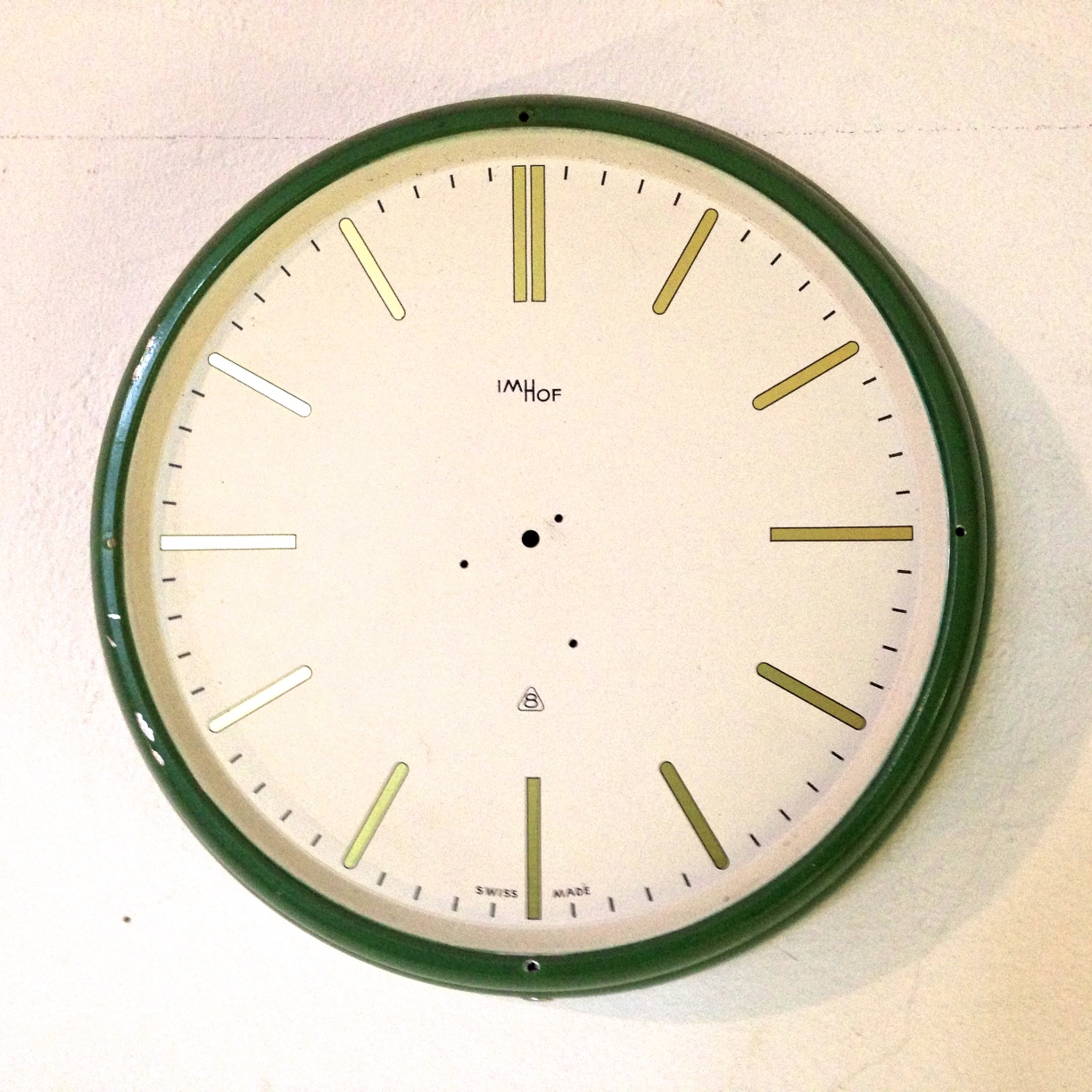 The clock pictured has no hands. Number positions one to eleven are marked with single vertical bars which look like the roman numeral for 1, the twelve position is marked with a double bar which looks like the numeral for 2.