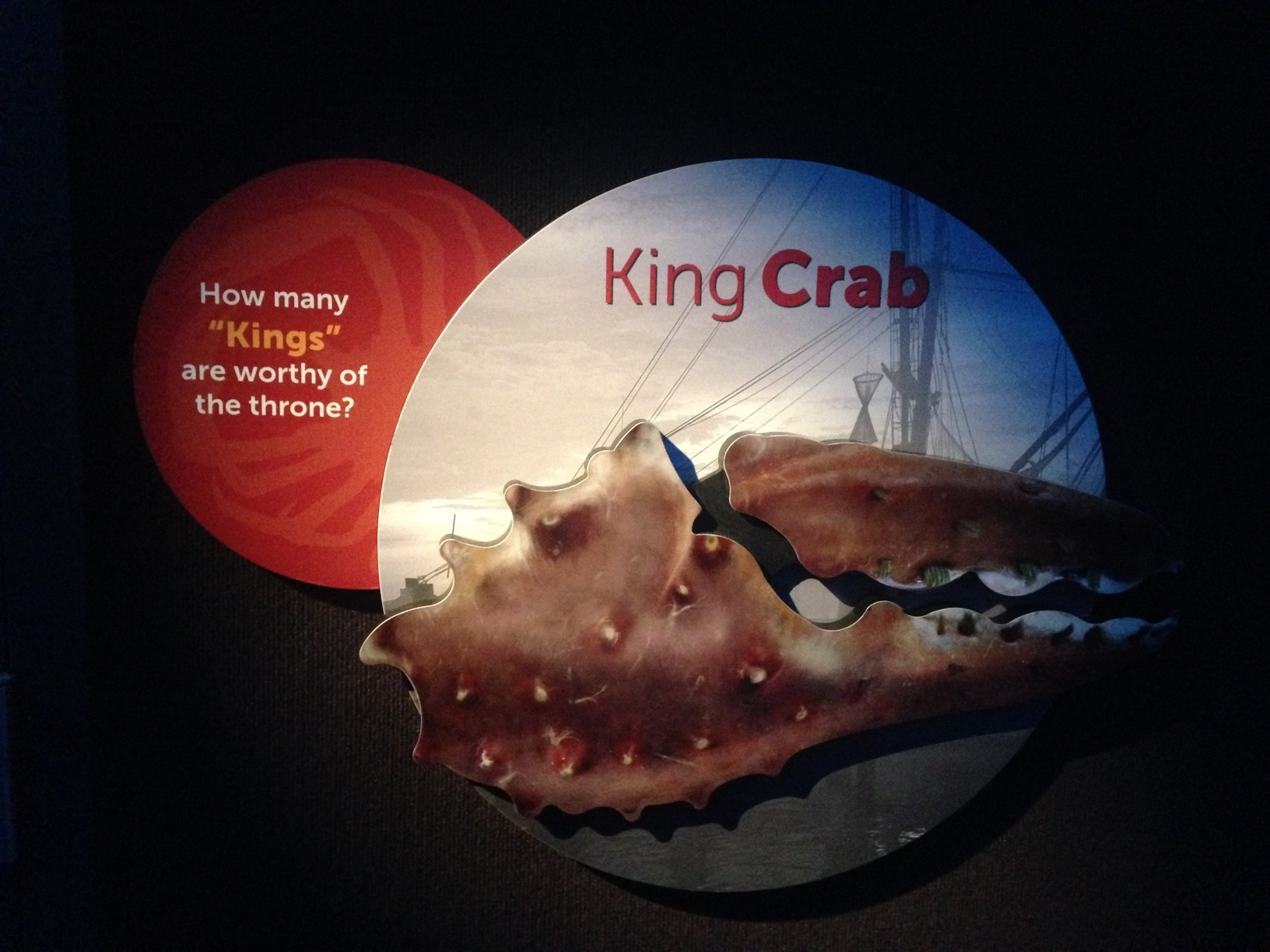 "The sign has a large crab claw against a background showing parts of a ship, and the text ""King Crab. how many kings are worthy of the throne?"""