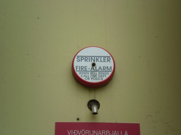 "A sign reading ""When alarm sounds, call fire department or police"""