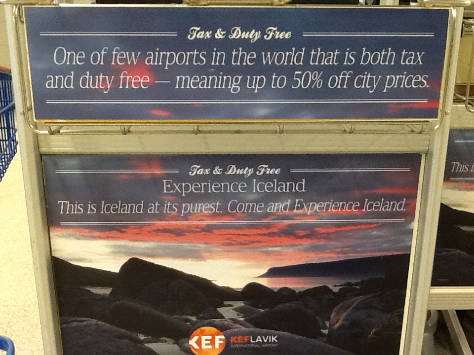 Sign reading: One of the few airports in the world which is both tax and duty free, meaning up to 50% off city prices. Experience Iceland. This is Iceland at it's purest. Come and Experience Iceland.