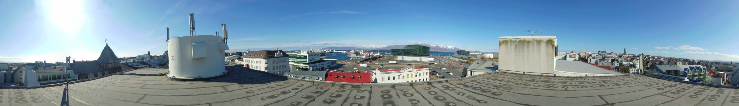 Some of the buildings on the high street are visible, the boats in the harbour are framed by mountains in the distance, as is the angular concert hall made of green glass.